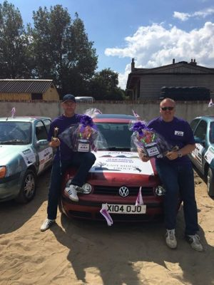 A photo of Wacky Racer's Malcom and Paul with their car and trophy, raising funds for Pancreatic Cancer Action