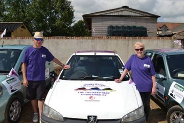 A photo of Wacky Racer's Phillip and June with their car and trophy, raising funds for Pancreatic Cancer Action