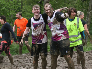 A photo of a pair of muddy supporters wearing Pancreatic Cancer Action running vests. They are taking part in Tough Mudder to raise funds for Pancreatic Cancer Action this New Year.