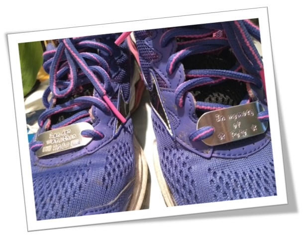 A picture of Laura Francis' trainers with remembrance plaques for her father-in-law, Pete