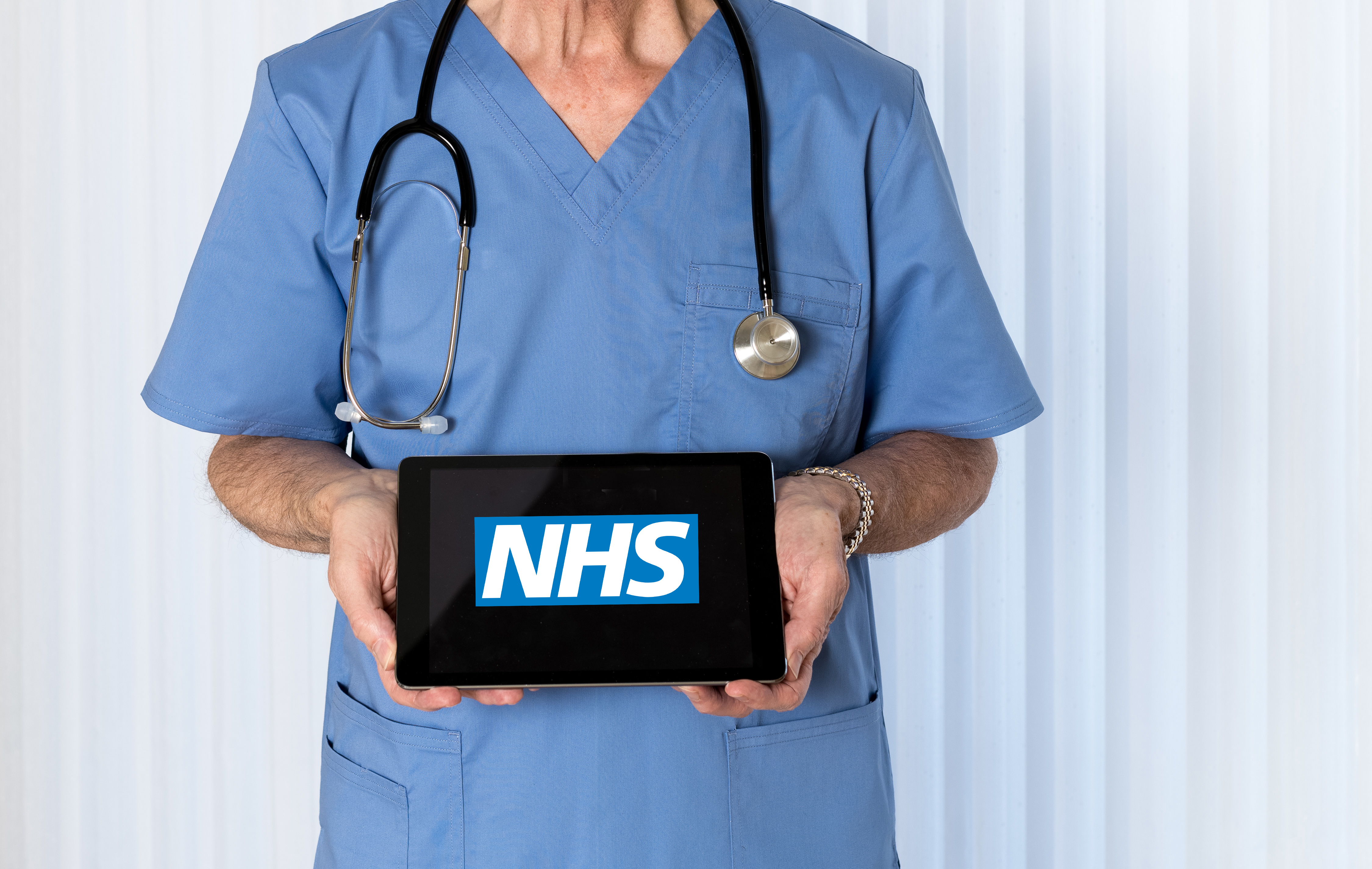 Senior male caucasian doctor with stethoscope in medical scrubs looking up and holding electronic tablet for NHS message