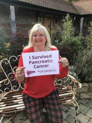 Gill holding a sign that says I survived pancreatic cancer