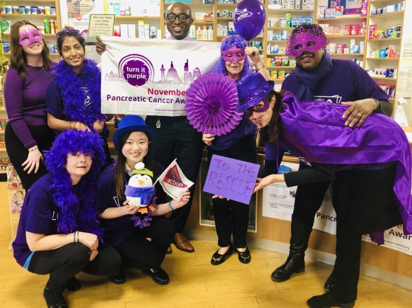 Bedminster Pharmacy wearing purple clothing and props