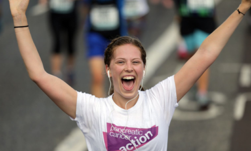 Woman wearing a PCA branded t-shirt celebrates completing a running event